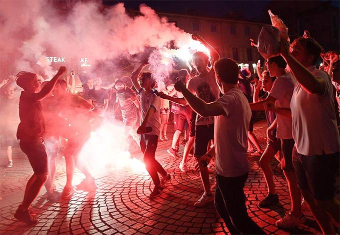 Một nhóm CĐV đốt pháo sáng, nhảy múa, hát ca ăn mừng.