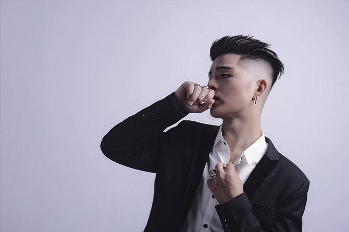 Quang Anh để kiểu tóc cá tính, đeo khuyên tai, trang điểm cầu kỳ, mắt đeo lens và tạo dáng rất ngầu trước ống kính.