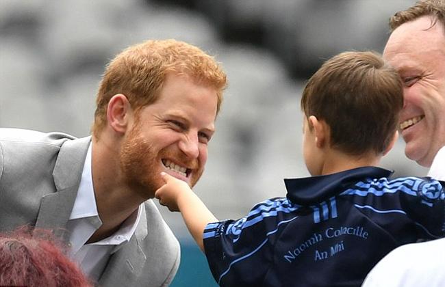 Harry giả vờ dọa một cậu bé khi được sờ râu. Ảnh: PA.