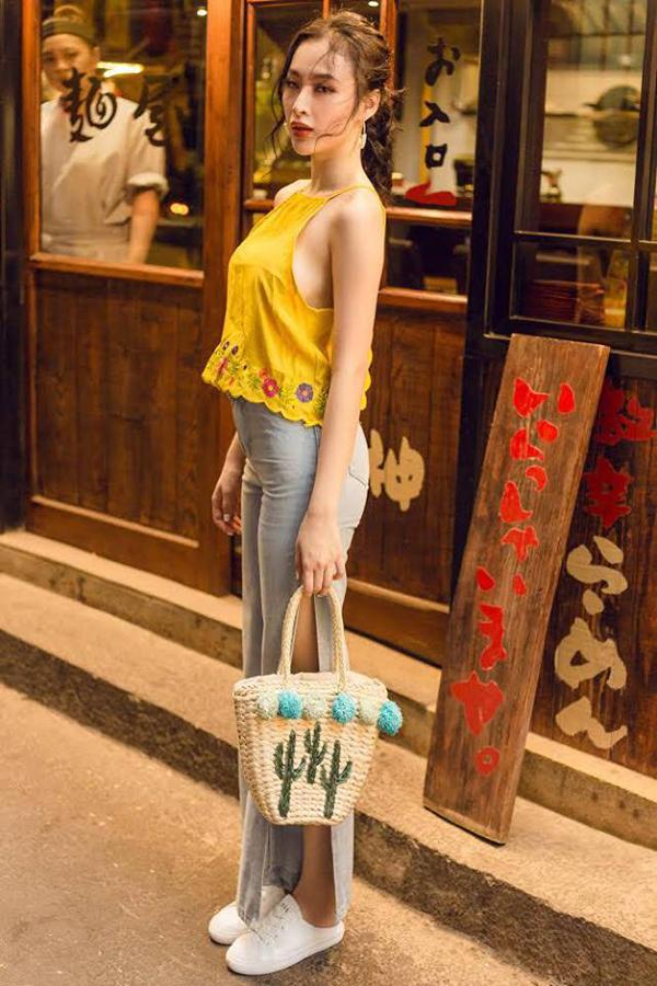 Đầu mùa nắng, Angela Phương Trinh nhanh tay chọn áo yếm tông màu hợp xu hướng phối cùng quần xẻ tà và túi cói.