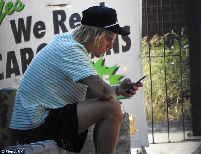 Justin Bieber trông nhăn nhó, bực dọc khi anh ngồi bên vỉa hè trò chuyện điện thoại hôm 12/7 ở New York. Ca sĩ 24 tuổi trông thất thần ngay cả khi cuộc trò chuyện điện thoại kết thúc, anh nhìn chằm chằm vào màn hình một lúc, sau đó còn lấy mũ che mặt để cánh paparazzi bớt chú ý.