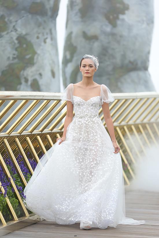 Trên cầu vàng - sàn catwalk dài gần 150 mét, trong ánh sáng tự nhiên của trời mây, từng người mẫu xuất hiện trong những thiết kế màu trắng tinh tế, đính kết cầu kỳ.