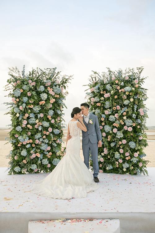 Uyên ương tổ chức hôn lễ hướng đến sự ấm cúng, đơn giản và lãng mạn. Cổng hoa nơi họ trao nhau lời hứa trọn đời được kết bởi hoa hồng phớt, cẩm tú cầu xanh và lá dương xỉ.