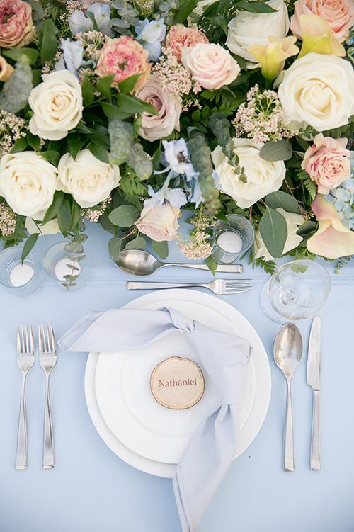 Mọi sự sắp đặt trong tiệc cưới đều tinh tế và nhẹ nhàng. Tên của chú rể được in trên lát cắt của thân cây gỗ, đem đến cảm giác mộc mạc, đơn giản.
