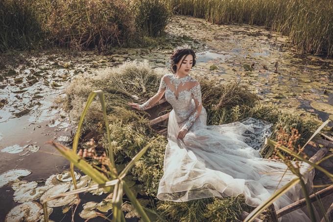 Vẫn gam màu trắng tin khôi, nhà thiết kế sử dụng chất liệu ren đắp nổi, tạo thêm điểm nhấn cho bộ váy.
