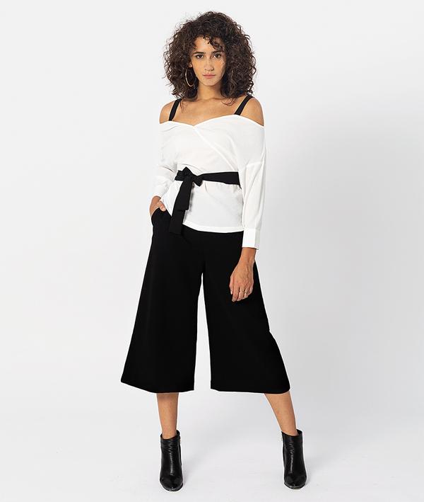 Phá cách với kiểu áo 2 dây trễ vai cùng phần thắt lưng biến tấu nơ. Áo được kết hợp vớiquần ống rộng thời thượng.