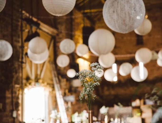 Không gian lắng đọng, hoài cổ với bức tường gạch màu nâu, đèn vàng và những chiếc đèn lồng treo lơ lửng.