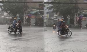 Bố chịu ướt mặc áo mưa cho con giữa đường