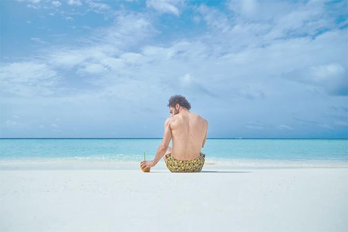 Chân sút của Liverpool ngồi một mình trên bãi biển, đăm chiêu nhìn vàotrái dừa. Bức ảnh này thu hút hơn 2 triệu lượt like.