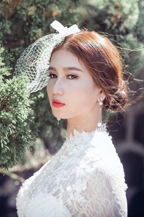 Trang phục của cô dâu mang nét hoài cổ với mạng che mặt ngắn, makeup nhấn mạnh vào đôi môi và tóc búi thấp.