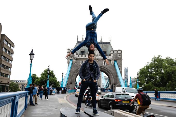 Một số người dân Anh kinh ngạc dừng bước,dùng điện thoại ghi lại cảnhhai nghệ sĩ châu Á thản nhiên biểu diễn mạo hiểm.