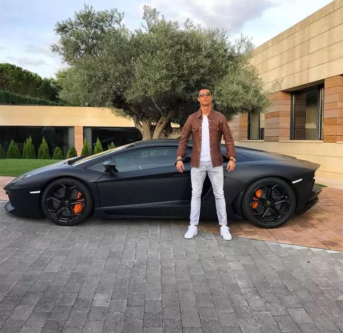 C. Ronaldo tạo dáng ngầu bên siêu xe Lamborghini đen mờ tại biệt thự ở Madrid. Sắp tới, siêu sao Bồ Đào Nha vận chuyển một số xe hơi của anh từ chỗ ở cũ tới Torino, Italy để phục vụ việc đi lại khi anh đến khoác áo Juventus.