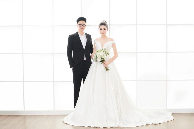 Dương Tú Anh chủ động đi giày bệt để không quá cao so với chồng. Váy cưới của nhà thiết kế (NTK) Lê Thanh Hòa giúp cô dâu khoe khéo vẻ gợi cảm. Người đẹp để tóc búi cao, đội vương miện và cách kết hợp phụ kiệnnày được cô tái sử dụng trong ngày cưới.
