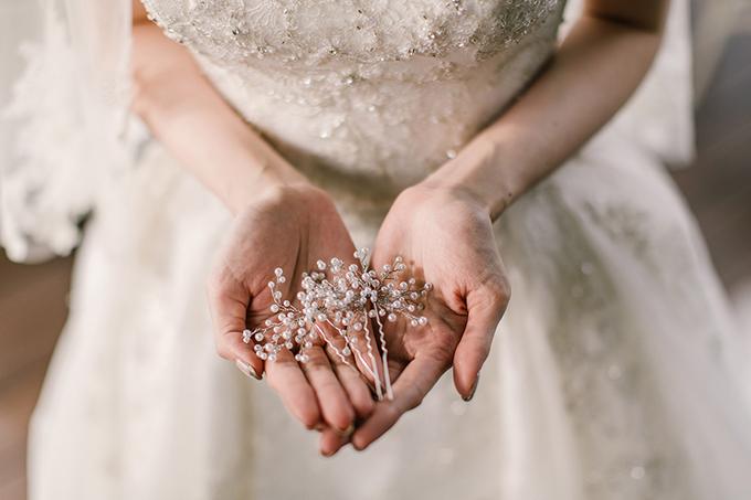 Cô dâu không chọn những phụ kiện cầu kỳ, rườm rà mà chỉ dùng cặp tăm có đính hạt ngọc nhỏ xinh cho mái tóc.
