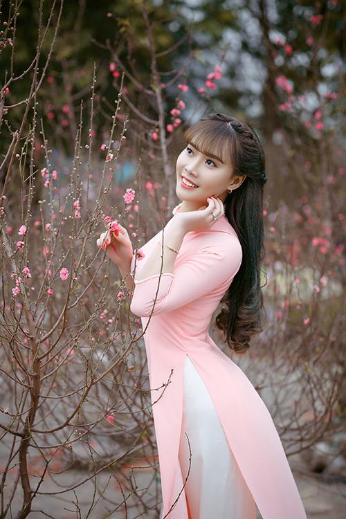 Cô dâu tạo dáng bên cành đào trong chợ hoa ngày Tết. Do sở hữu studio chụp hình ở Ninh Bình và có sở thích bấm máy nên lúc nào rảnh, tôi thường dẫn cô ấy đi chụp ảnh rồi tổng hợp tất cả thành album ảnh cưới, chú rể cho hay.