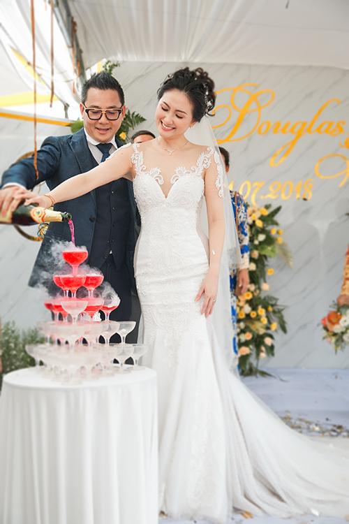 Cô dâu diện chiếc váy ren trắng thứ hai để rót rượu làm lễ và tiếp khách. Váy cưới có cổ illusion (cổ voan mờ ảo) để khoe vòng ngực đầy mà không phản cảm. Ngang hông váy được thiết kế hiệu ứng 3D ngụy trang cho vòng hai trở nên thon gọn hơn.