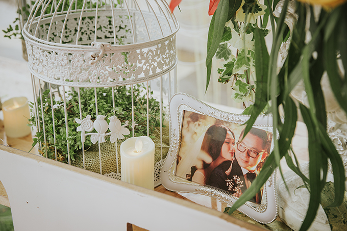 Bàn tiếp tân tiệc cưới nhà cô dâu được trang trí bởi ảnh cưới phong cách Hàn Quốc của hai vợ chồng, nến trắng, nhành lá đơn giản và những lồng chim được sơn trắng, ngầm thể hiện uyên ương đã về chung một nhà.