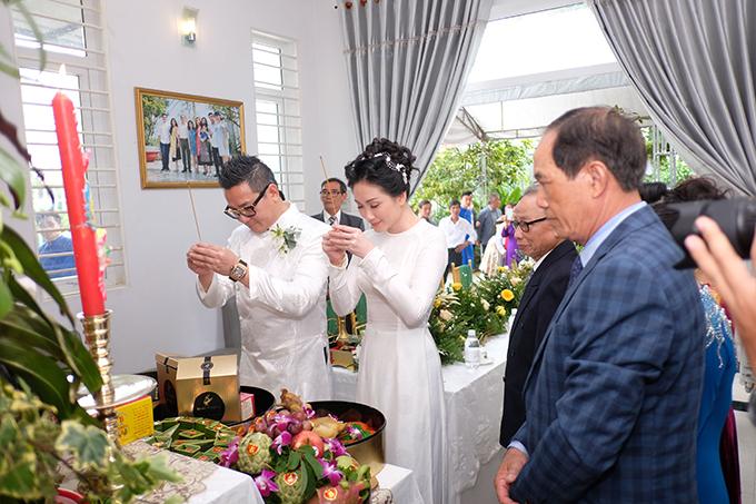 Uyên ương chọn áo dài trắng đơn giản để thực hiện nghi thức cúng bái tổ tiên.