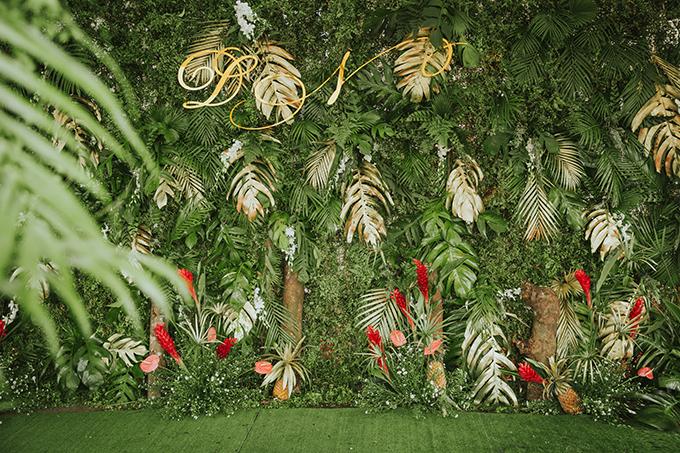 Phông nền đám cưới được tạo nên từ các loại lá cây rừng nhiệt đới, dứa, hoa hạnh phúc, hồng mônđỏ...