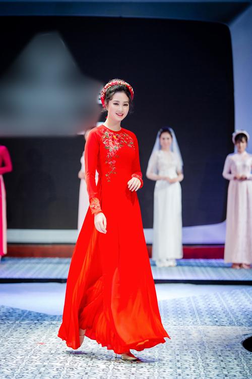 Theo quan niệm của người Á Đông, màu đỏ tượng trưng cho sựmay mắn. Do đó, các cô dâu thường chọn màu đỏ cho trang phục cưới hỏi. Người mẫumặc áo dài có thiết kế cổ tròn, chân váy xếp li đỏ tươi cùng tông áo dài và mấn có họa tiết thêu nổi.Để tạo điểm nhấn mang phong cách retro, nhà thiết kế đã thêuhọa tiếtthịnh hành trong những năm 1980 - 1990 lên ngực áo và cổ tay áo.