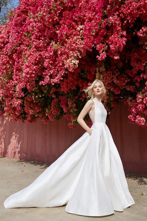 Váy cưới được làm từ chất liệu tafta cao cấp vàthiết kếcổ thuyền, gợi sự sang trọng, thanh lịch. Phần voan mờ từ ngang ngực tới hông vừa tạo vẻ đẹp kín đáo mà quyến rũ cho nàng dâu mới.