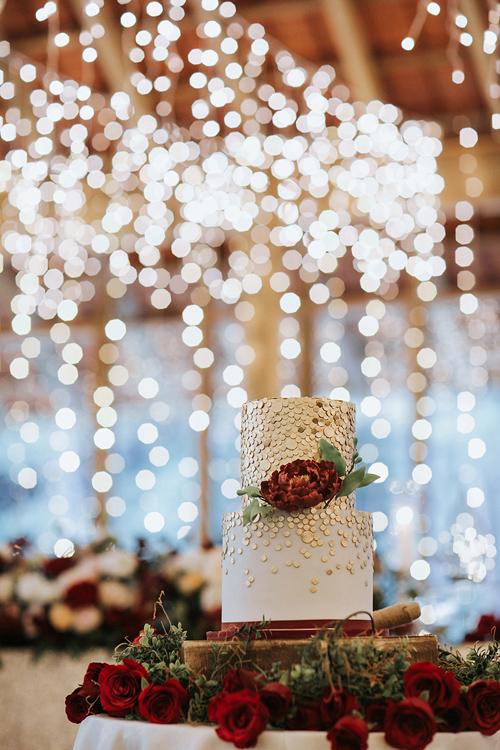 Bánh cưới hai tầng của uyên ương được điểm thêm các hạt lấp lánh màu vàng đồng và một đóa mẫu đơn đỏ tía, là điểm nhấn thú vị, phá cách cho hôn lễ.