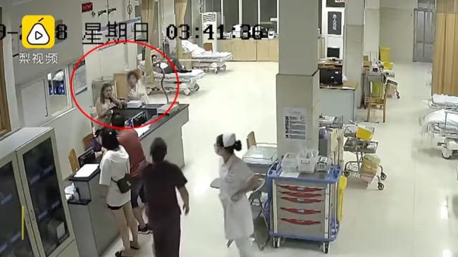 Nạn nhân bị rắn cắn (khoanh đỏ)giơ cao con rắn trên tay để ra hiệu cấp cứu gấptại bệnh viện Kim Hoa chiều29/7. Ảnh cắt từ video.