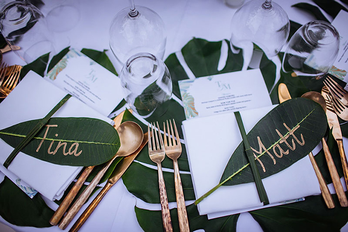 Để làm nổi bật khu rừng này, wedding planner đã viết tên khách mời bằng mực màu vàng đồng lên trên những chiếc lá cây. Họ còn chọn bộ dao nĩa cùng tông màu với chữ viết thể hiện sự tinh tế, hiện đại.
