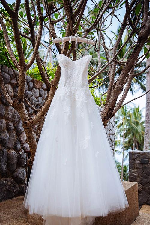 Váy cưới của cô dâu có dáng chữ A xòe nhẹ, được đắp ren ở thân trên và điểm xuyết hoa văn ở thân dưới.