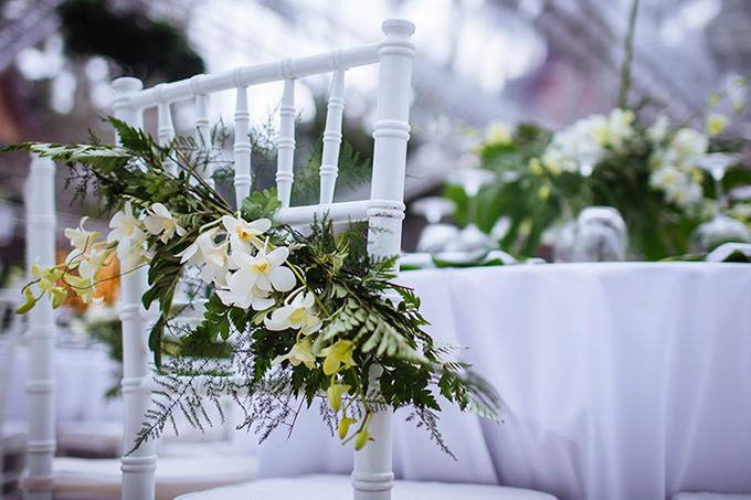 Ghế ngồi của khách mời được trang trí hoa lan hồ điệp trắng, sắc xanh từ nhành lá nhỏ đem đến cảm giác về một khu rừng thanh mát.
