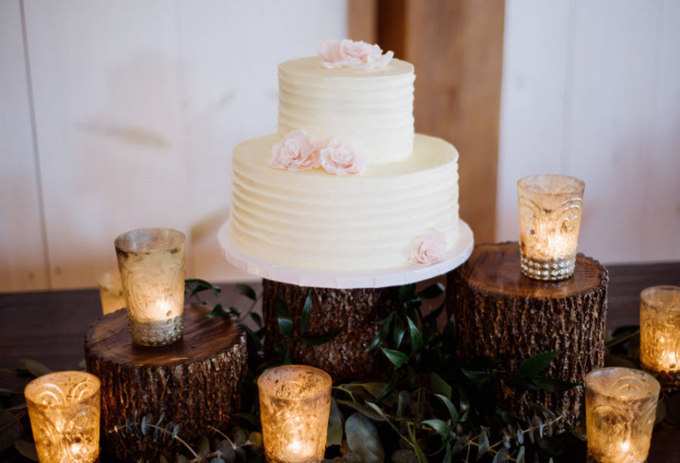 Bánh cưới không có hình mô phỏng cặp vợ chồng hoặc ký tự viết tắttên của uyên ương: Đểbánh cưới thêm đơn giản và sang trọng, thợ làm bánh dùng nĩa tạo kết cấu cho hai tầng bánh và dùng hoa màu hồng nhạt để trang trí.