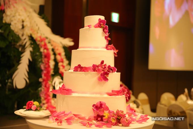 Bánh cưới 5 tầng của uyên ương mang sắc trắng chủ đạo và được điểm thêm những cánh sen hồng và bông hoa lan.
