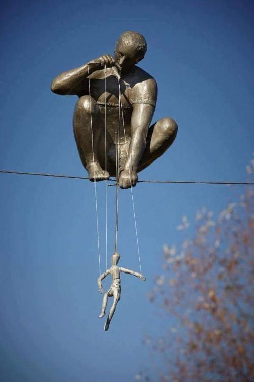 Tác phẩm tượng đồng lơ lửng trên dây điện mô phỏng một người đàn ông đang chơi con rối do nghệ sĩJerzy Kedziora hoàn thành tại công viên Ann Norton Sculpture Gardens, Palm Beach, Florida, Mỹ,