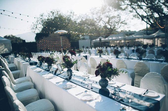 Uyên ương chọn bàn tiệc dài để khách mời có thể dễ dàng quan sát cô dâu chú rể từ phía xa. Mỗi bàn tiệc phục vụ từ 8-10 suất ăn và được tô điểm bởi một bình hoa hồng đỏ thắm.