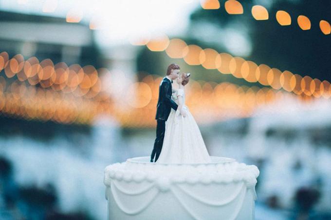 Tượng mô phỏng hai vợ chồng được đặt ở tầng trên cùng của bánh cưới. Để tạo ra không gian tiệc cổ điển, uyên ương trang trí bánh cưới với đường nét hoa văn nhẹ nhàng, mềm mại.