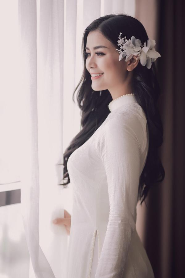 Nữ diễn viên Dốc sương mù chọn áo dài trắng đính ngọc trai để hòa hợp với phong cách giản dị của lễ vu quy. Diệu Thúy không đeo nhiều trang sức cầu kỳ mà chọn một châm cài làm điệu cho mái tóc dài xoăn nhẹ trong ngày làm cô dâu.