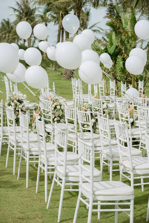 Wedding planner buộc 100 quả bóng bay màu trắng vào ghế ngồi. Sau khi kết thúc buổi lễ, 100 quả bóng sẽ được thả lên trời, gửi gắm lời chúc hạnh phúc trăm năm của khách mời tới cô dâu chú rể.