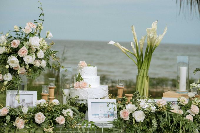 Bánh cưới của hai vợ chồng khá đơn giản với sắc trắng và được điểm thêmmột vài bông hồng nhạt, phù hợp với yêu cầu bài tríđơn giản, thanh lịch của cô dâu.