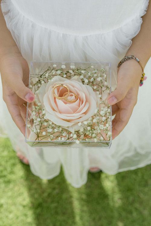 Đôi nhẫn của uyên ương được đặt trong chiếc hộp hoa hồng trong suốt, là điểm nhấn thú vị trong buổi lễ.