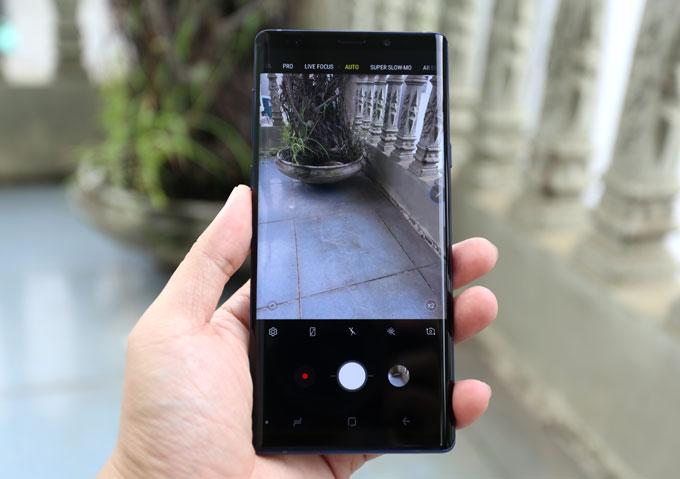 Note 9 có camera kép cùng độ phân giải 12MP có thể thay đổi khẩu độ f/1.5 đến f/2.4. Camera kép phục vụ mục đích chụp ảnh xoá phông và zoom quang 2x. Camera này cũng có tính năng ổn định hình ảnh quang học (OIS). Điểm cải tiến đáng chú ý nhất trên camera Note 9 là tính năng AI, tự động nhận diện 20 khung cảnh khác nhau để tối ưu hình ảnh, cho ảnh đẹp hơn. Trong hình trên, camera Note 9 nhận diện khung cảnh là cỏ cây hoa lá (biểu tượng hai chiếc lá trên khung chụp ảnh), chắc hẳn sẽ làm màu lá xanh hơn, màu sắc khác rực rỡ hơn.