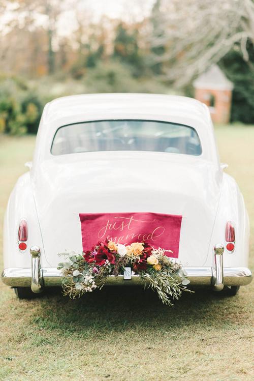 2. Tấm thẻ thông báo tình trạng mới kết hôn bằng vải có màu sắc sặc sỡ trên chiếc xe cổ màu trắng. Phông chữ mềm được sử dụng kết hợpvới một khóm hoa rực rỡ.