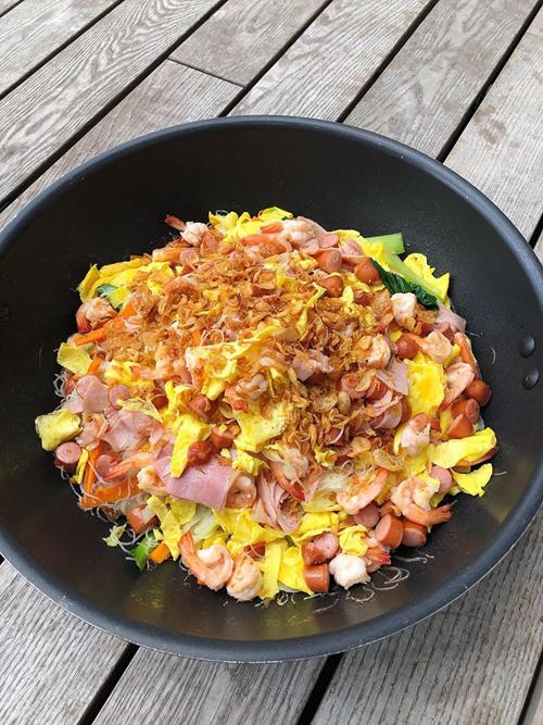 Bún khô xào hỗn hợp tôm trứng, xúc xích, hành khô và rau củ.