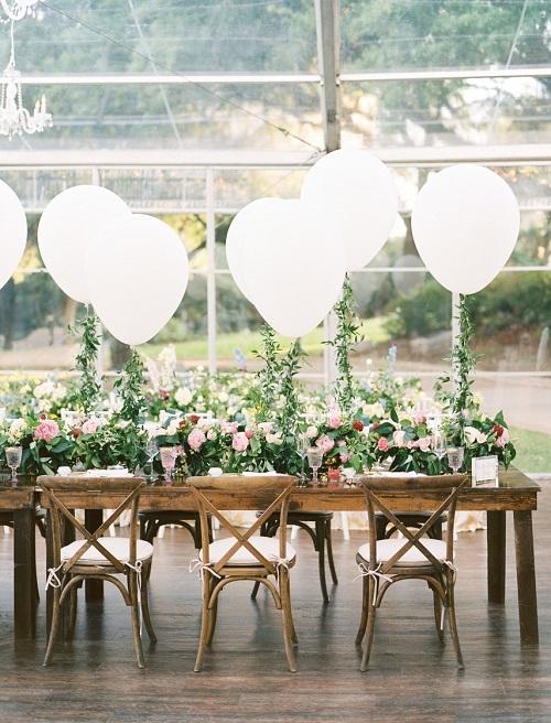 Khách mời dễ dàng lạc vào khu vườn địa đàng xinh đẹp với bàn ăn đầy hoa và những chiếc bóng bay cỡ lớn. Sử dụng lá cây che dây bóng, bữa tiệc cổ tích dành riêng cho các cô dâu lãng mạng, bay bổng. Ảnh:Ben Q Photography