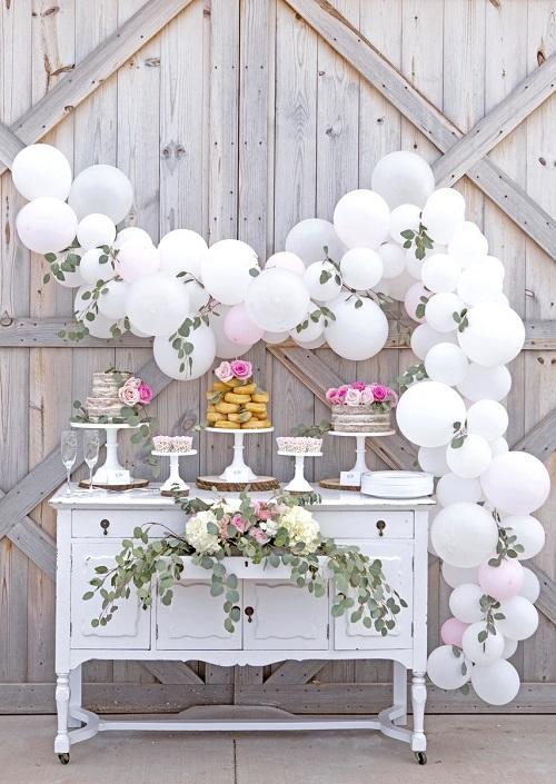 Những quả bóng trắng, hồng phấnnhẹ nhàng xen kẽ vài cành lá kết hợp với hoa tươi tại bàn đồ ngọt. Trên nền gỗ nhạt, các chi tiết nổi bật vẻ trang nhã, dịu dàng cho tiệc cưới lãng mạn. Ảnh:Lillian Hope Designs