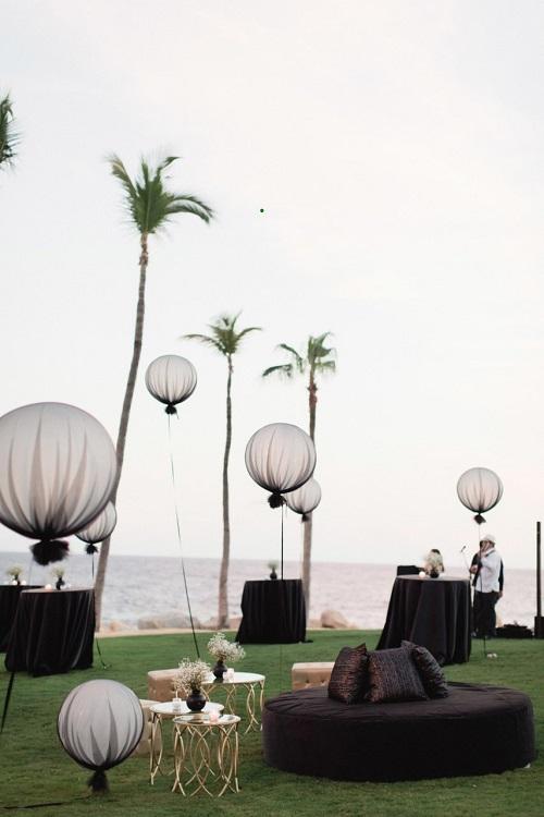 Thời thượng và khác biệt, những chiếc bóng bay lớn bọc trong lớp vải tuynở các độ cao khác nhau kết hợp cùng tấm trải bàn, ghế ngồi đen ánh vàng.Trên bờ biển lãng mạn, chi tiết trang trí có phần đối lập tạo nên một sự hài hòa mới mẻ cho bữa tiệc. Ảnh:Lucas Griffin