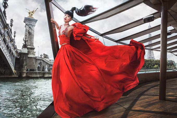 Trước khi tổ chức show diễn trên thuyền ở Paris, Jessica Minh Anh thực hiện bộ ảnh thời trang ấn tượng. Cô mặc váy dạ hội đỏ rực, tạo dáng trên con tàu đang chạy quanh sông Seine.