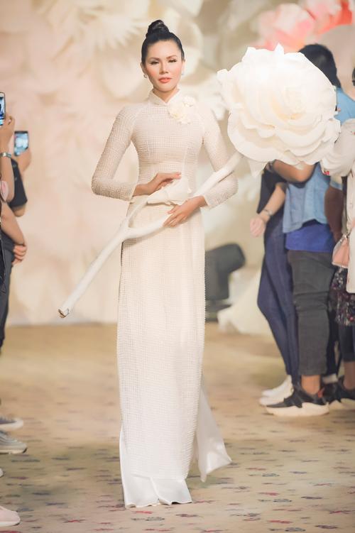 Chất liệu vải lưới vốn được cho là không phù hợp để tạo nên một bộ trang phục trang trọng, kín đáo như áo dài. Tuy nhiên, nhà thiết kế đã đem đến một cách nhìn khác khi điểm xuyết những bông hoa nổi 3D để hướng sự chú ý của người đối diện vào phần vai áo. Chất liệu được dệt riêng cho bộ sưu tập đảm bảo độ nhẹ và bay bổng.