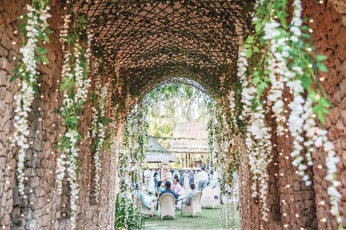 Lối đi dẫn vào không gian tiệc được trang hoàng bởi hoa tươi, dây leo và những dây đèn treo.