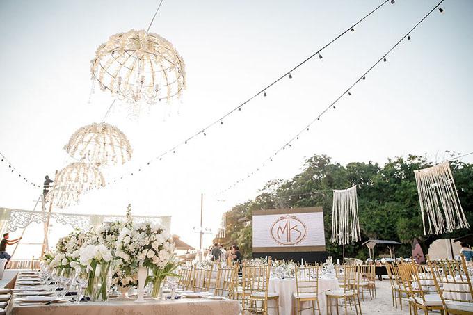 Không gian sảnh tiệc được thắp sáng bởi đèn dây và đèn chùm. Cặp vợ chồng dùng ghế Tiffany (Chiavari) để tăng thêm sự sang trọng.