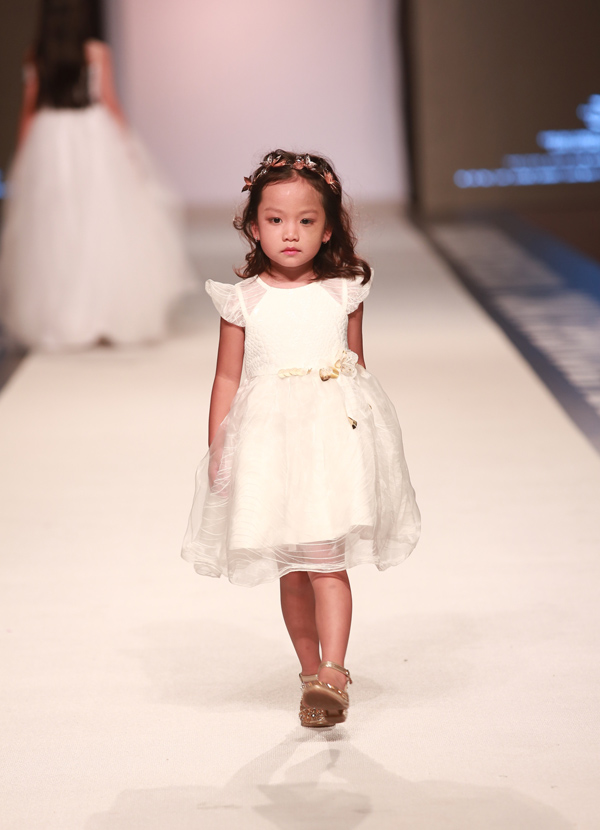Mẫu nhí đáng yêu như búp bê khi mặc váy dạ hội trắng catwalk tự tin. Hồng Khánh từng chụp lookbook cho một thương hiệu nước ngoài và biểu diễn tại các show thời trang trong nước.
